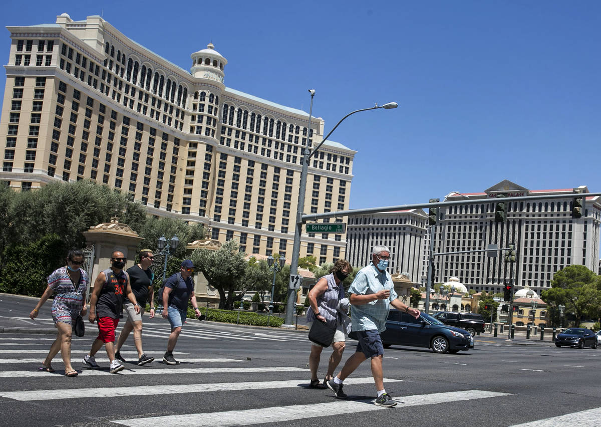 Tourists cross Las Vegas Boulevard near the Bellagio on Friday, July 3, 2020, in Las Vegas. (Bi ...