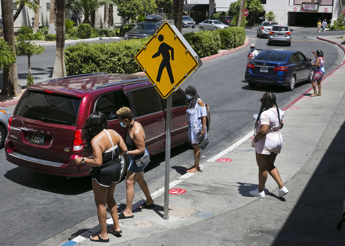 Tourists wait for their ride at ride sharing pick up area outside of the Flamingo on Friday, Ju ...