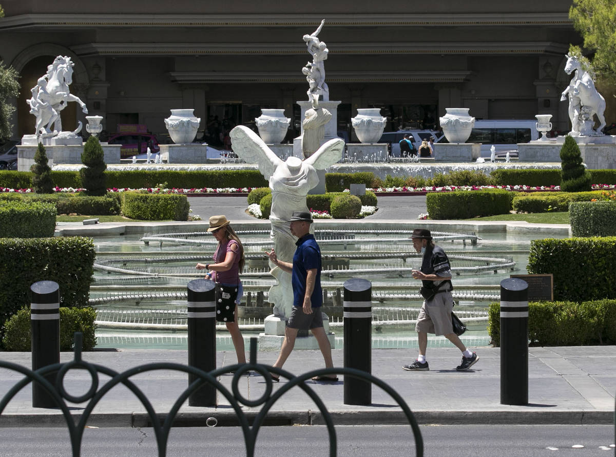 Tourists walk past Caesars Palace fountains on Friday, July 3, 2020, in Las Vegas. (Bizuayehu T ...