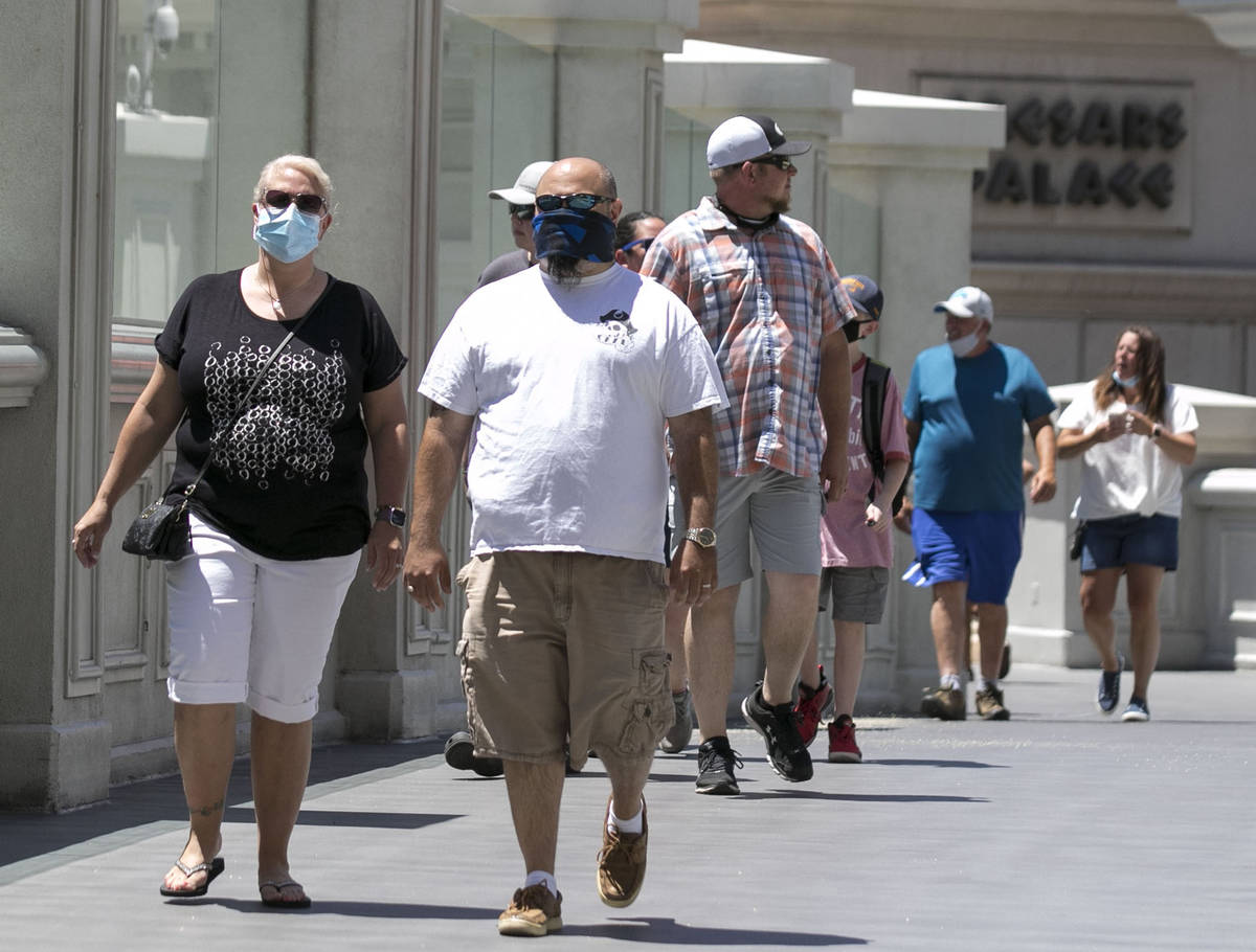 Tourists walk on the pedestrian bridge between Caesars Palace and The Flamingo on Friday, July ...
