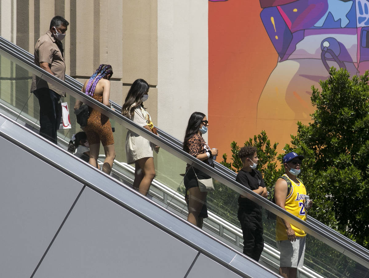 Tourists use an escalator near New York-New York and the MGM Grand on Friday, July 3, 2020, in ...