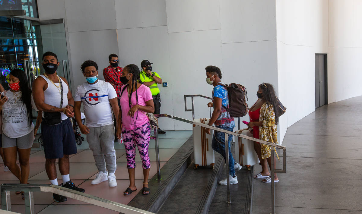 Marcus Battle and Whitney Brown bring their bags up the stairs to Sahara Las Vegas as other tou ...