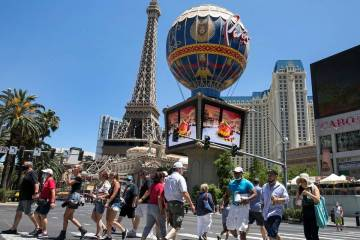 Tourists cross Las Vegas Boulevard near Paris hotel-casino on Friday, July 3, 2020, in Las Veg ...