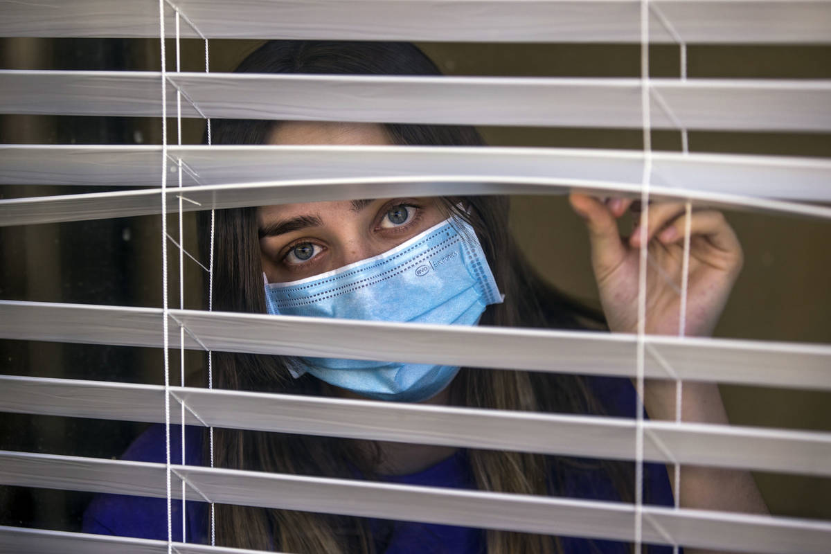 Kaydee Asher, 16, behind a window, is currently fighting the coronavirus and quarantined at hom ...