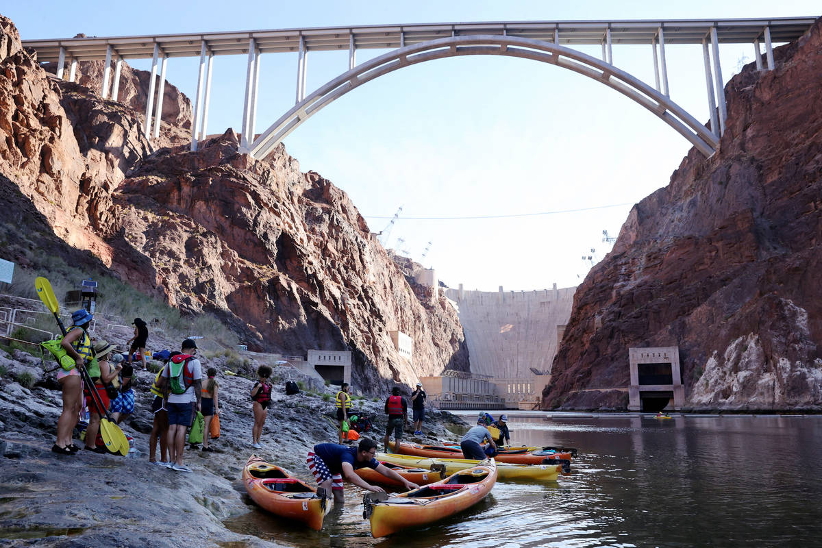 People prepare for a day of kayaking in Black Canyon at the base of the Hoover Dam with Desert ...