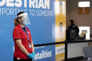 An employee wears a face shield, mask and gloves while working at the Nevada Department of Moto ...