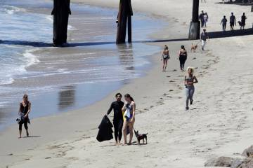 Visitors walk and exercise on the beach Wednesday, May 13, 2020, in Malibu, Calif. (AP Photo/Ma ...