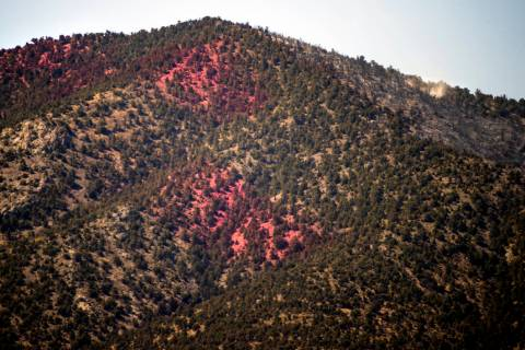 Fire retardant covers a hillside and fire smolders on the upside of it during the Mahogany Fire ...