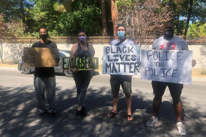 Kenny Fawkes and Sam McKellar, standing to the left, pose with other protesters in Las Vegas Ma ...