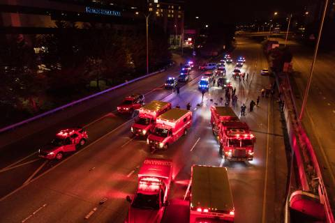 Emergency personnel work at the site where a driver sped through a protest-related closure on t ...