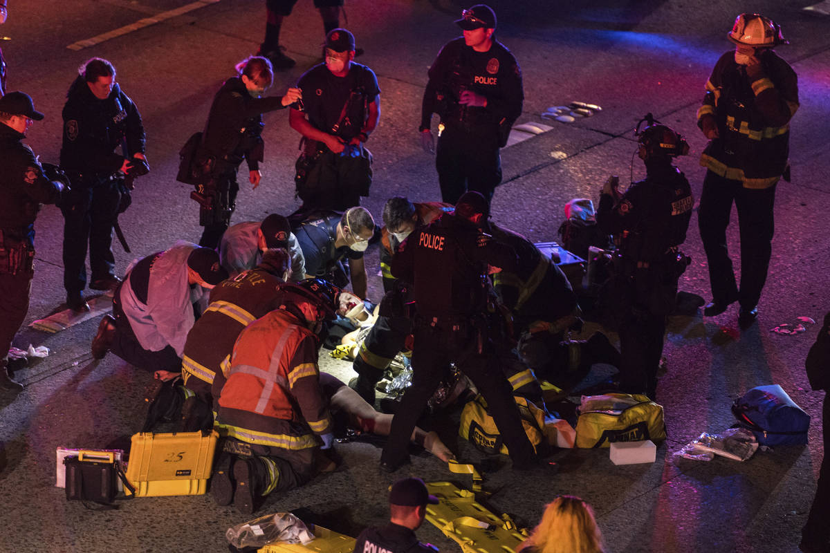 Emergency workers tend to an injured person on the ground after a driver sped through a protest ...