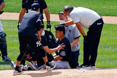 New York Yankees pitcher Masahiro Tanaka is tended to by team medical personnel after being hit ...