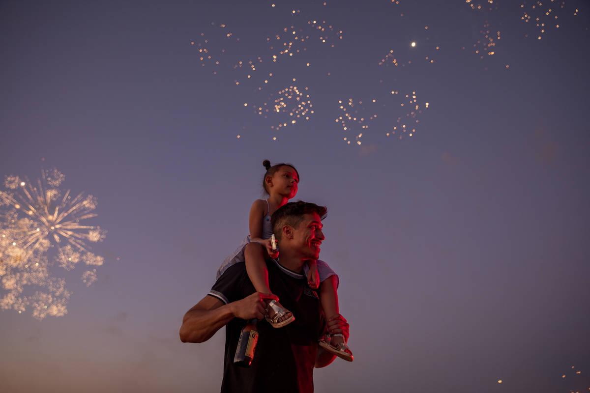 Mathew Laspina carries Arzaylea Laspina, 5, of Las Vegas, as they watch fireworks near Moapa Pa ...