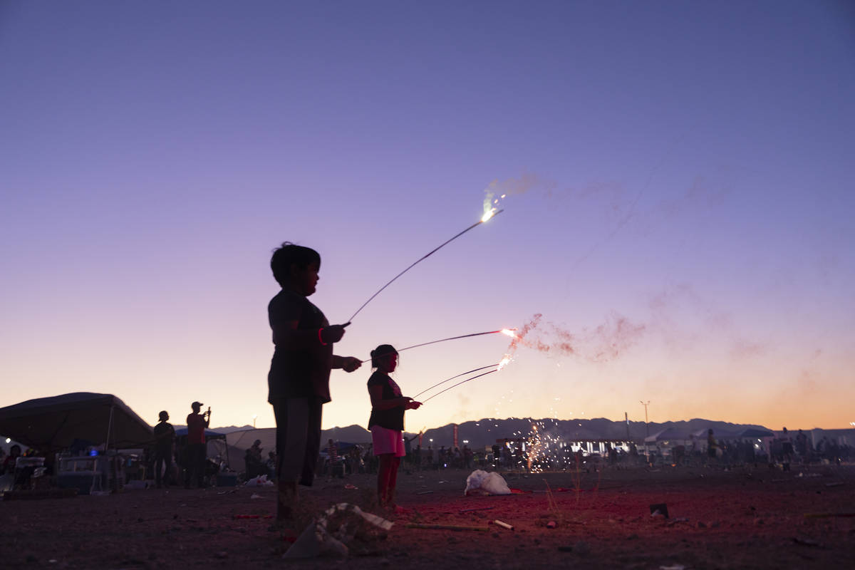 Individuals light off fireworks near Moapa Paiute Travel Plaza during Fourth of July festivitie ...