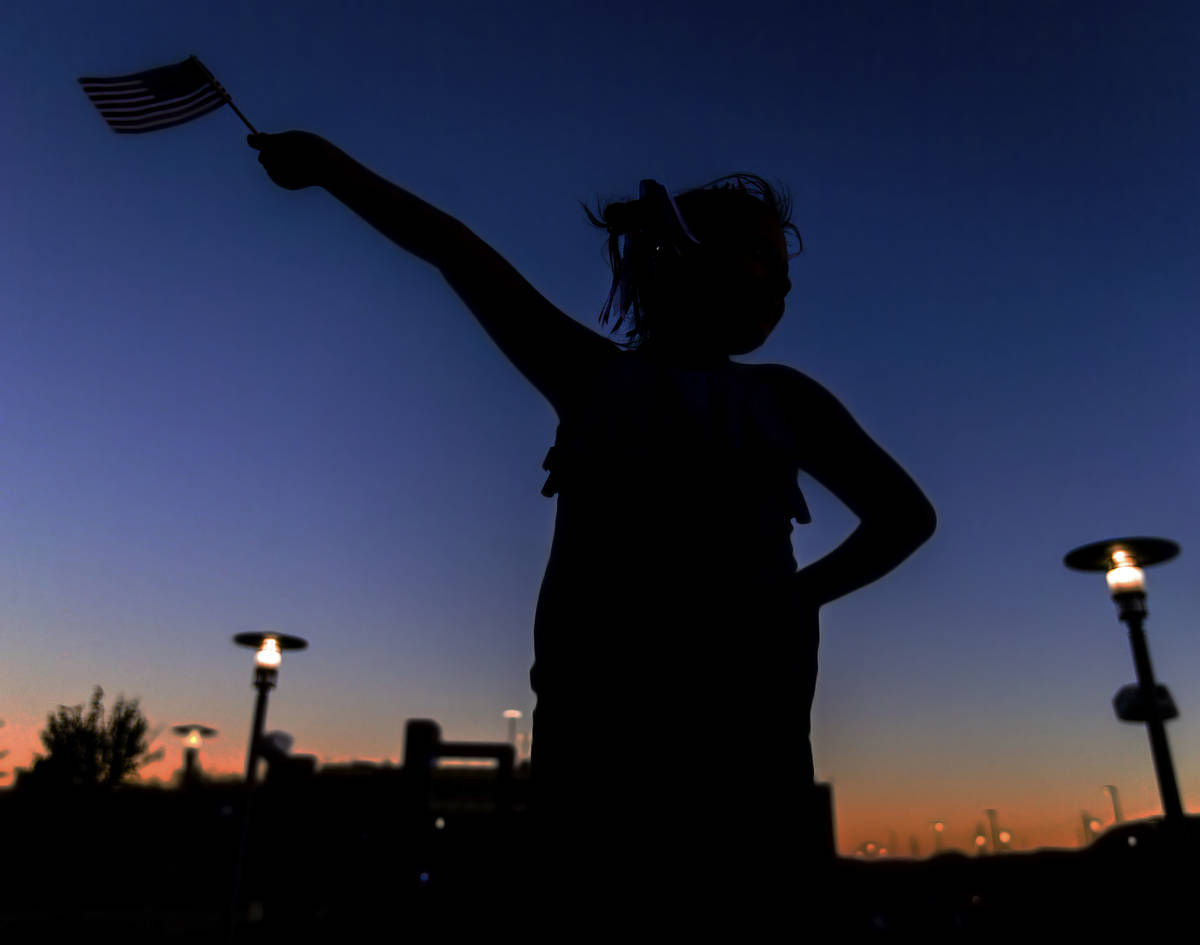 Rylee Wilkerson, 9, waves an American flag while she waits for the start of the Red Rock Casino ...