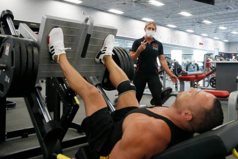 A trainer, top, at Mountainside Fitness, works with a client as the facility remains open even ...