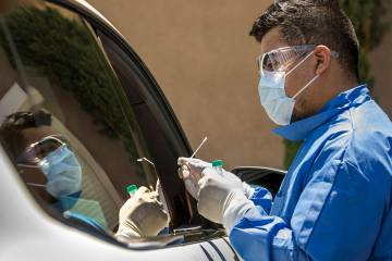 Practice Manager Jose Tirana conducts a COVID-19 test on a patient in the parking lot at Sahara ...