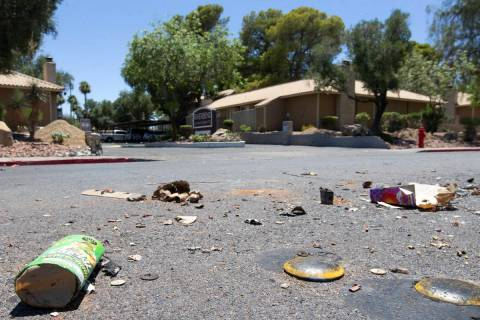 Exploded fireworks litter the street next to Riverbend Village Apartments, which was the site o ...
