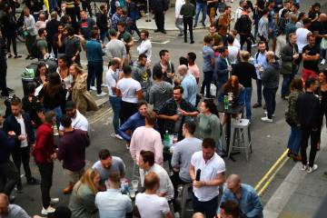 Drinkers in Soho congregate, as coronavirus lockdown restrictions eased across England, in Lond ...