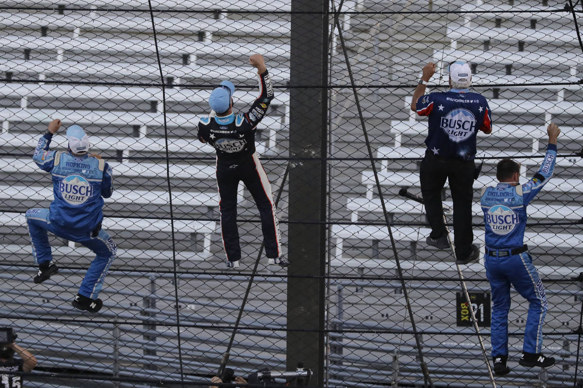 Kevin Harvick, second from left, and some members of the team's crew climb the fence after Harv ...