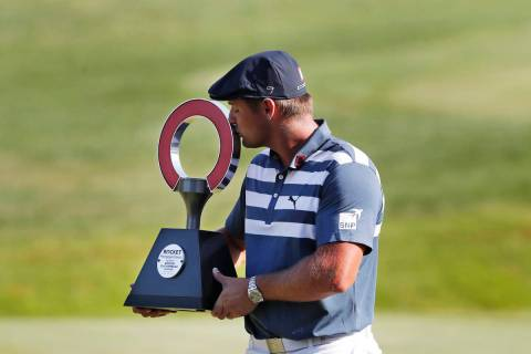 Bryson DeChambeau kisses the Rocket Mortgage Classic golf tournament trophy Sunday, July 5, 202 ...
