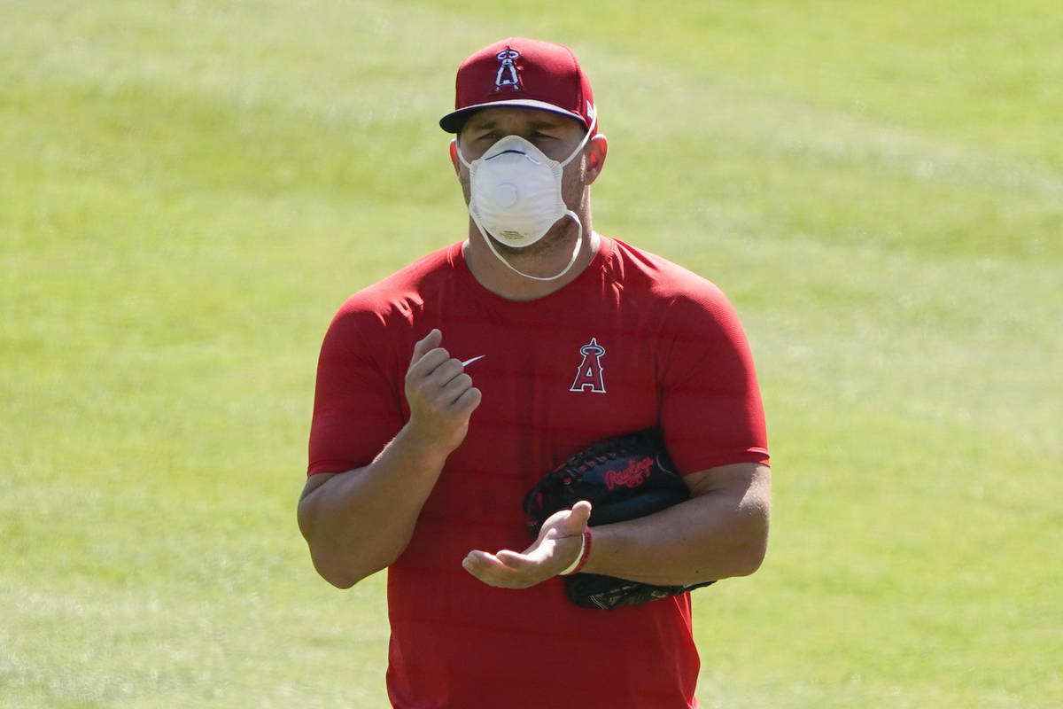Los Angeles Angels center fielder Mike Trout (27) stands on the field wearing a face mask durin ...