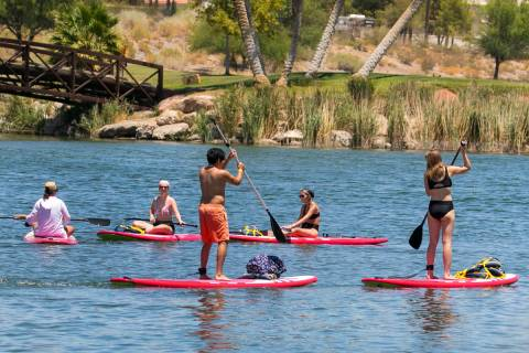 People take advantage of the hot weather to enjoy paddle boarding at Lake Las Vegas on Monday, ...