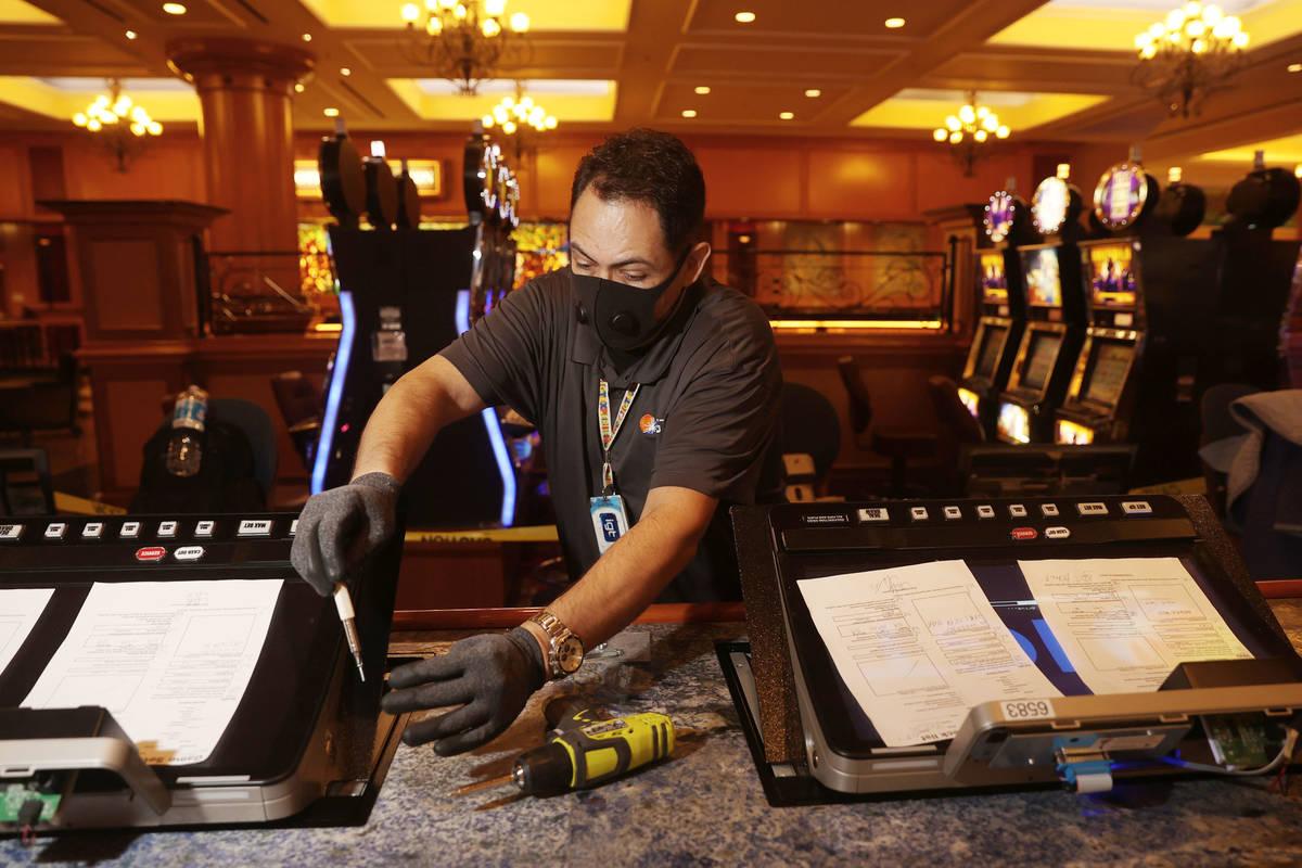 International Game Technology technician Saul Rivera installs PeakBarTop slot machine cabinets ...