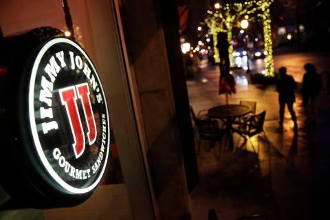 Pedestrians pass by a Jimmy John's sandwich shop, Friday, Jan. 2, 2015, in Atlanta. (AP Photo/D ...