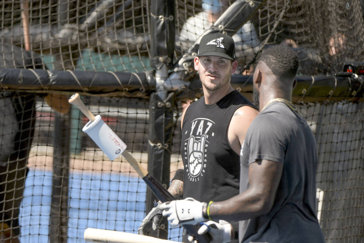 Chicago White Sox Yasmani Grandal, left, talks with teammate Luis Robert, right, during batting ...