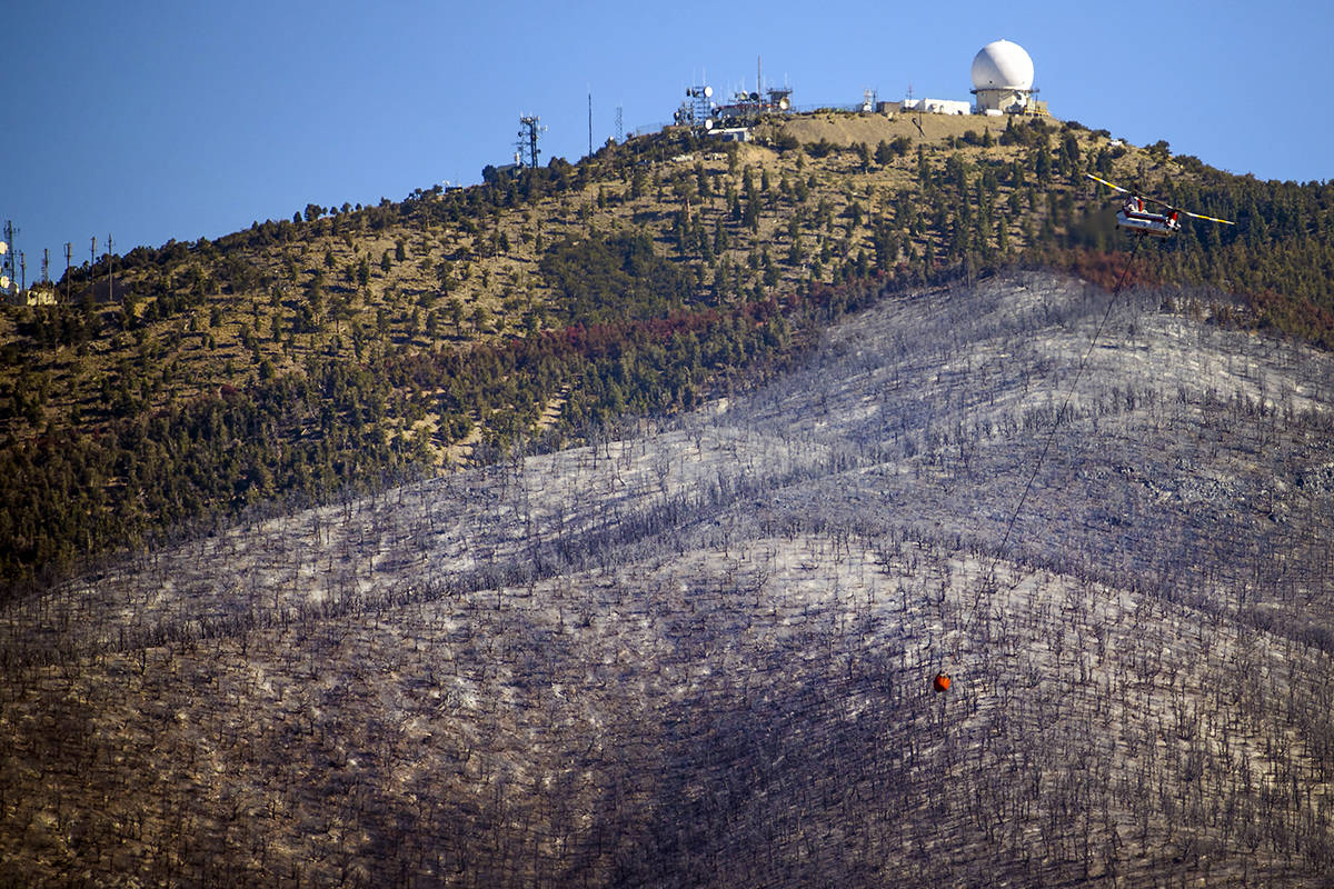 A helicopter with water bucket returns for another drop over the Mahogany Fire on Mount Charles ...