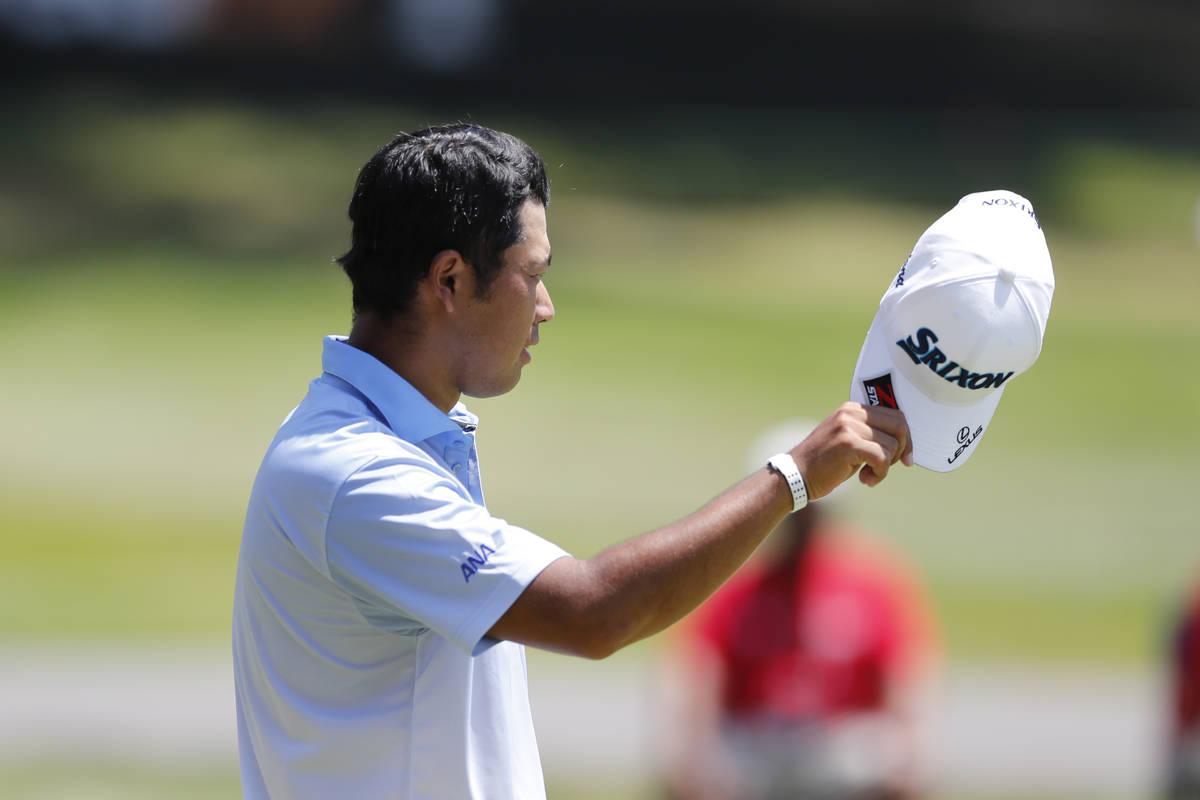 Hideki Matsuyama of Japan talks tips his cap to player partner, Luke Donald on the 18th green d ...