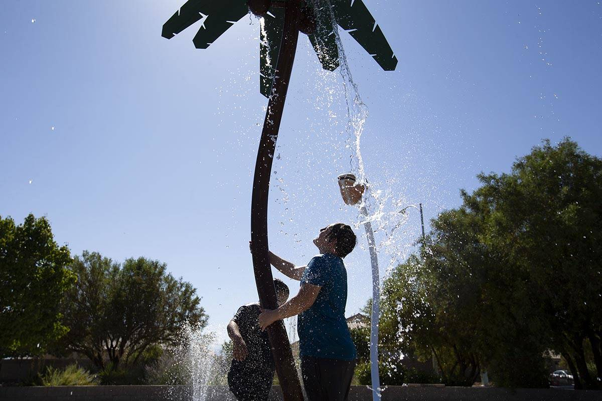 Carlos Contreras, left, 9, and his brother Edwin Contreras, right, 11, wait for water to fall f ...