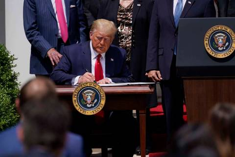 President Donald Trump signs the Paycheck Protection Program Flexibility Act during a news conf ...