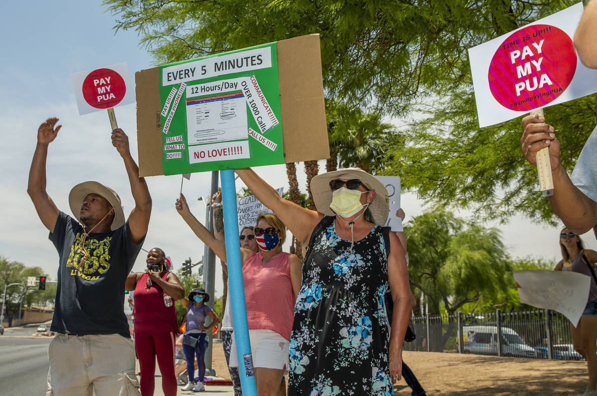 Gig workers gather with signs and wave to passing motorists along E. Washington Ave. to protest ...