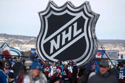 In this Feb. 15, 2020, file photo, fans pose below the NHL league logo at a display outside Fal ...