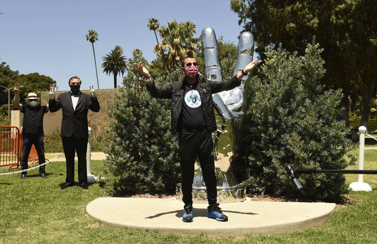 """Musician Ringo Starr poses in front of his """"Peace and Love"""" sculpture on his 80th bir ..."""