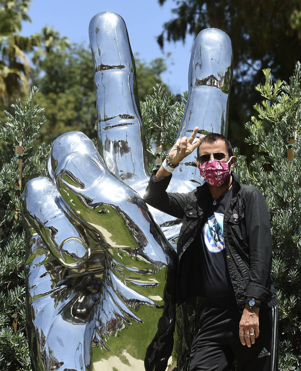 """Musician Ringo Starr poses in front of his """"Peace and Love"""" public sculpture on his 8 ..."""