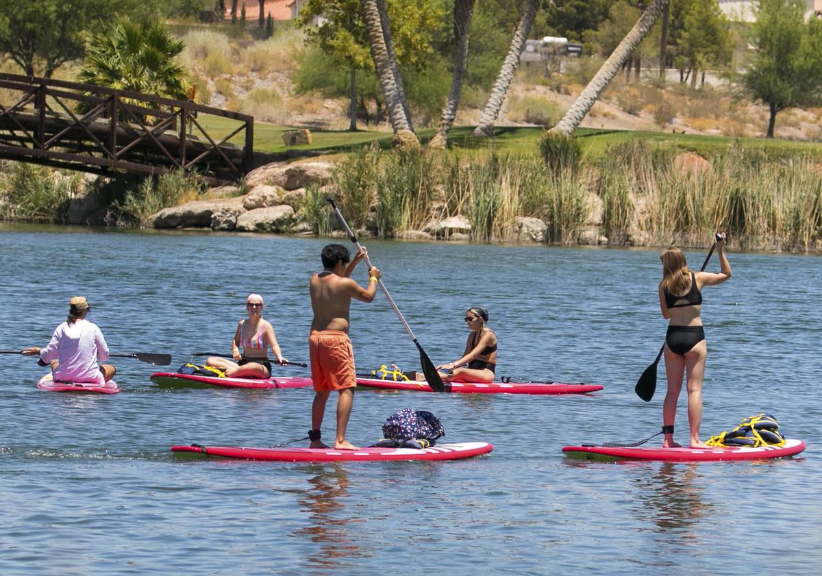 People take advantage of the hot weather to enjoy paddle boarding at Lake Las Vegas on Monday, ...