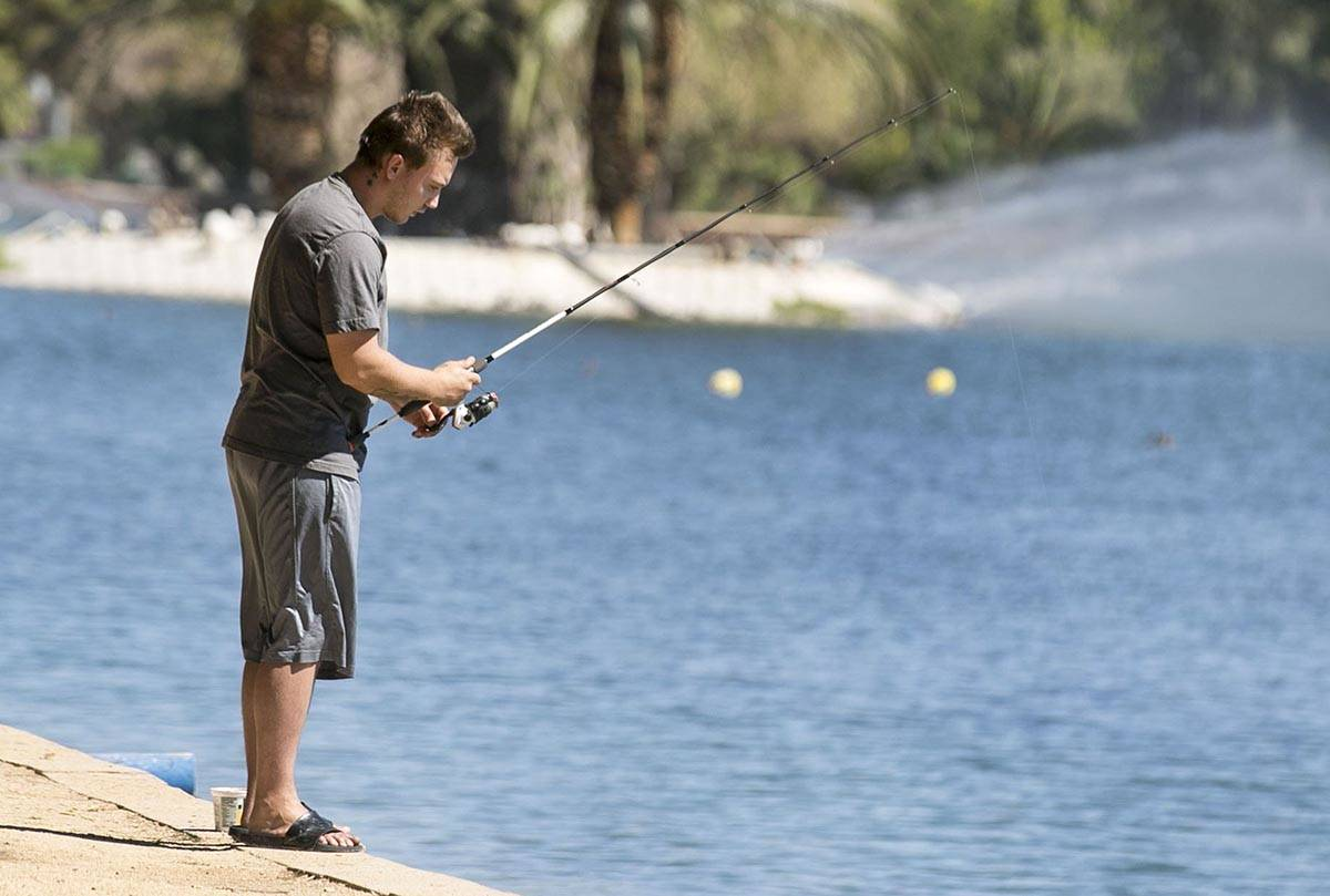 Zack Sutherland fishes at Sunset Park on Wednesday, July 8, 2020, in Las Vegas. The forecast hi ...