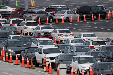 Lines of cars wait at a drive-through coronavirus testing site, Sunday, July 5, 2020, outside H ...