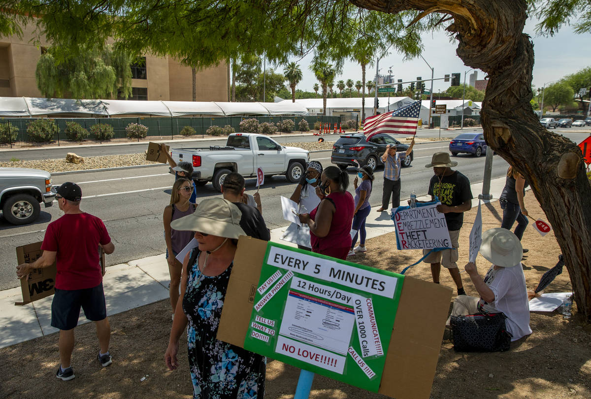Gig workers gather with signs wave to passing motorists along E. Washington Ave. to protest the ...