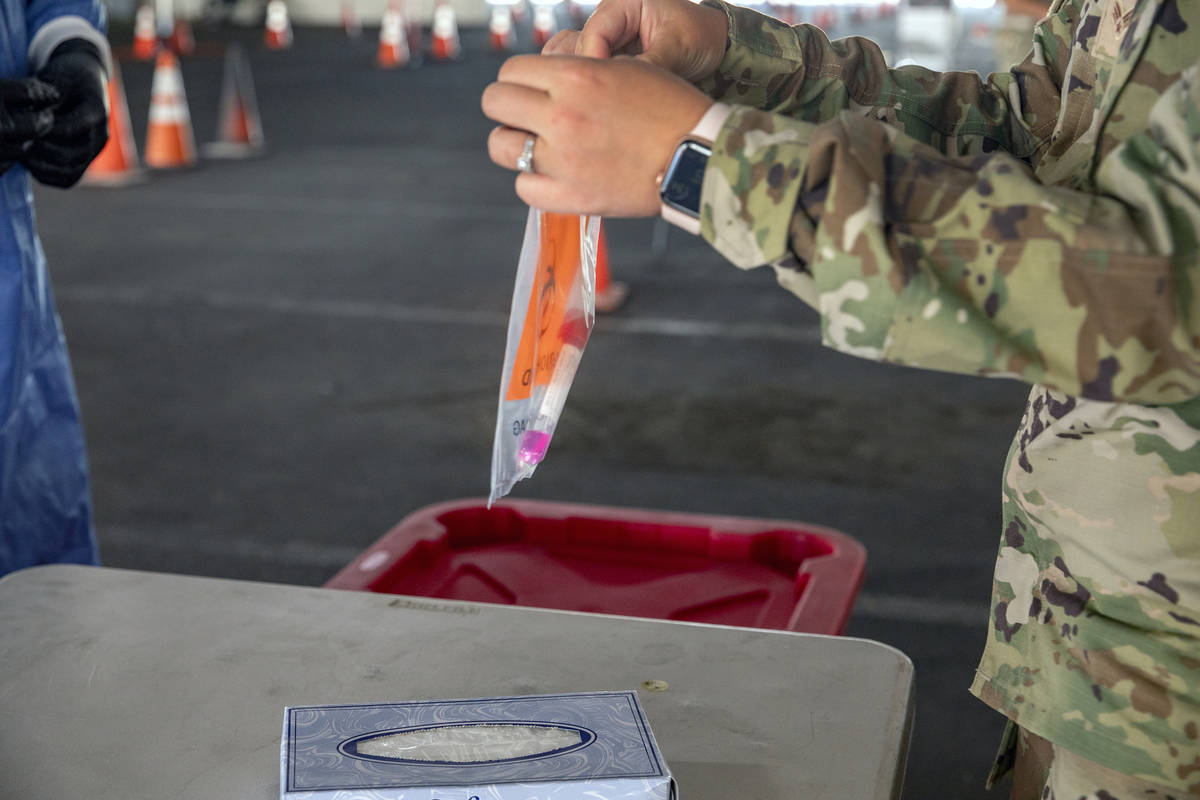 A Nevada National Guardsmen combat medic seals a plastic bag with a COVID-19 test used in a dem ...