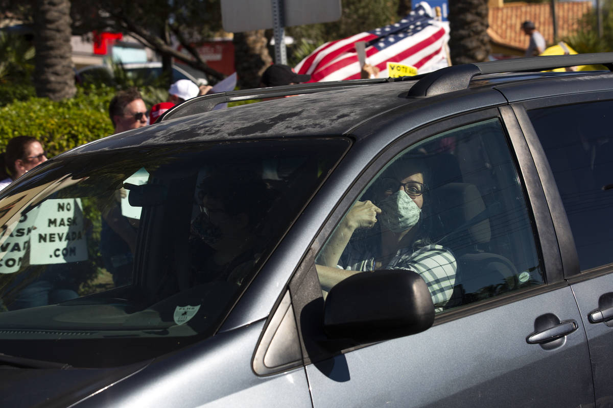 """A passing motorist points to her mask as she passes the """"No Mask Protest"""" at the intersection o ..."""