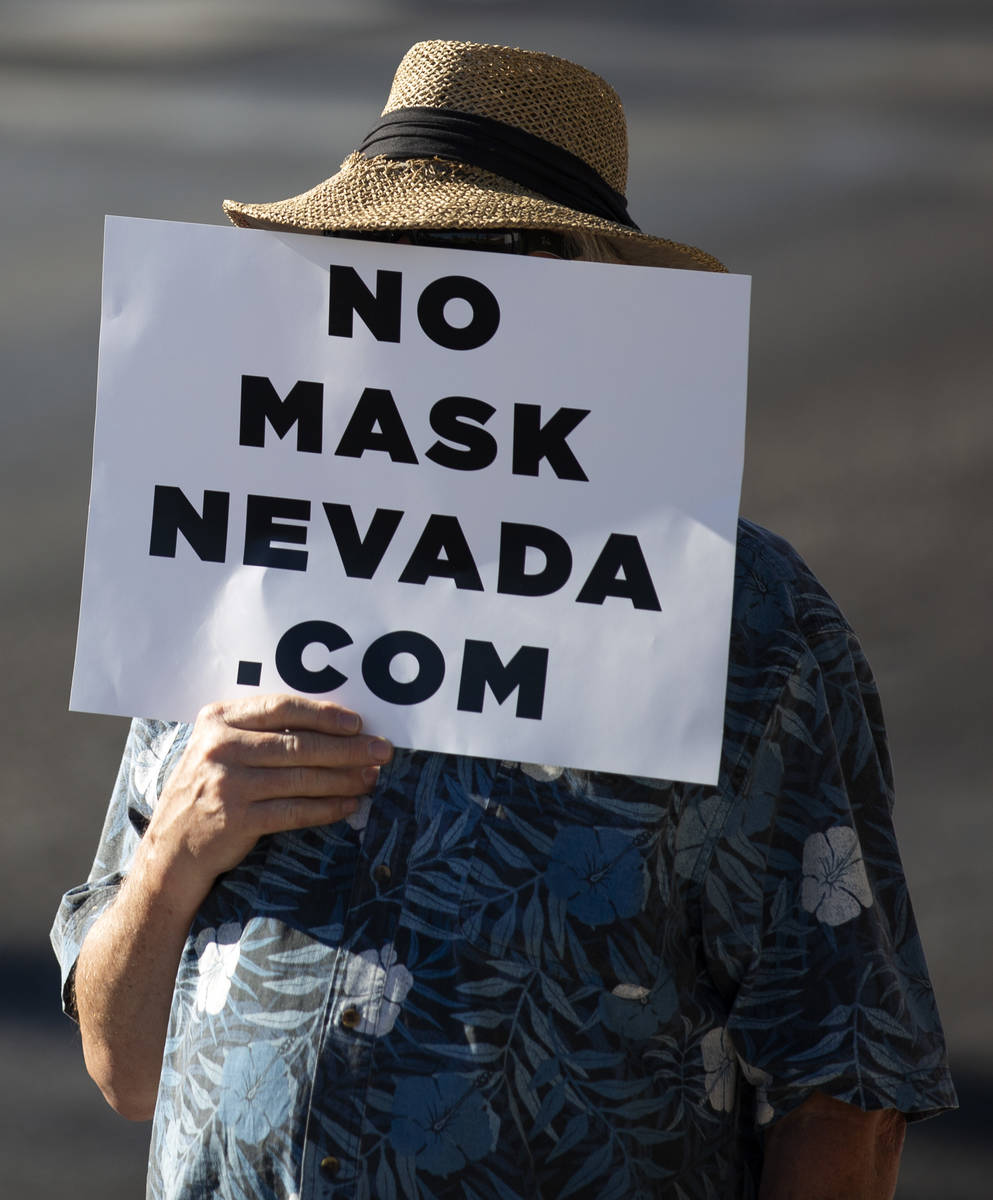 """A protester covers his face with a sign during the """"No Mask Protest"""" at the intersection of Wes ..."""