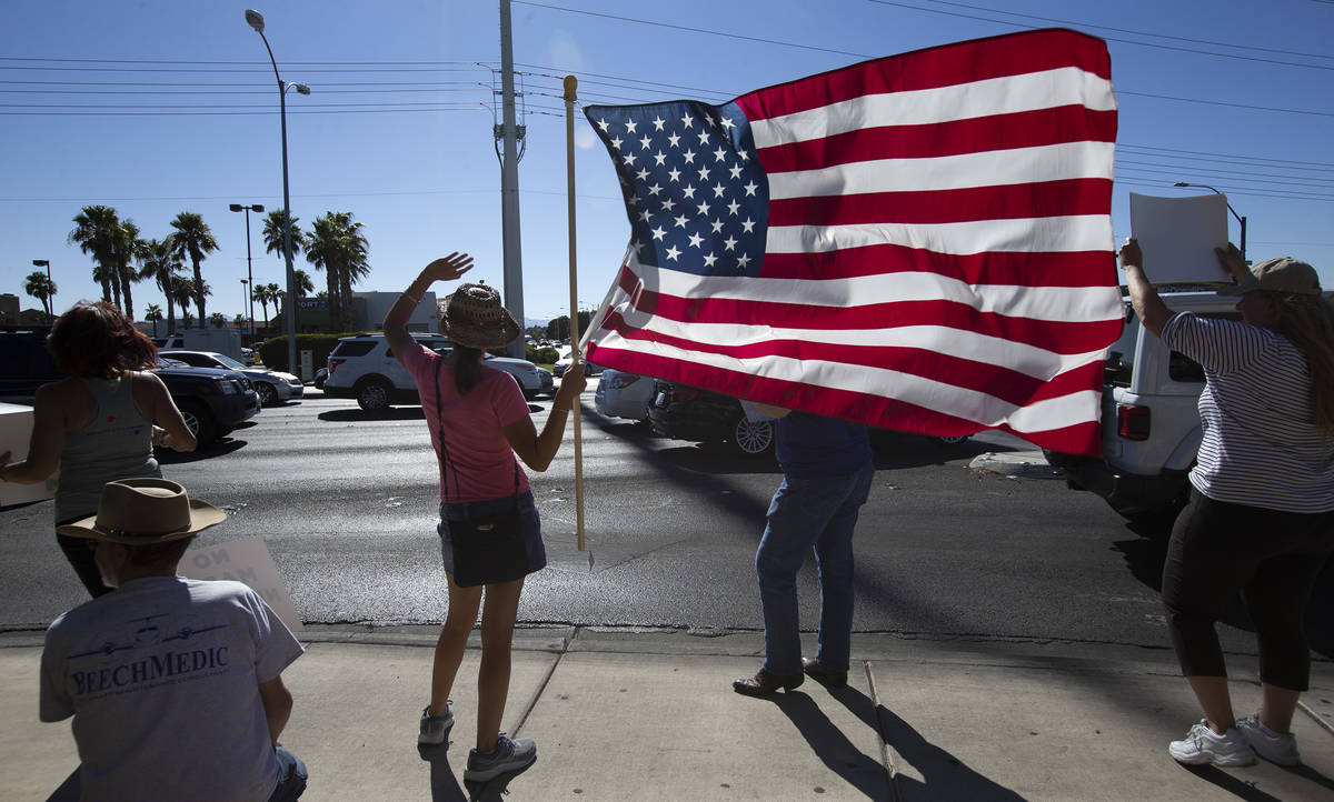 """Faith Duello, second from left, holds an American Flag at the """"No Mask Protest"""" at the intersec ..."""