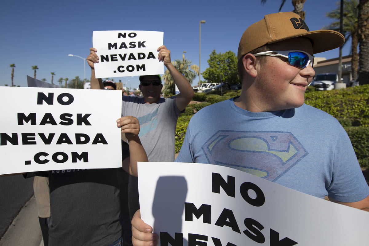 """James Thiriot, right, 15, participates in the """"No Mask Protest"""" at the intersection of West Sun ..."""