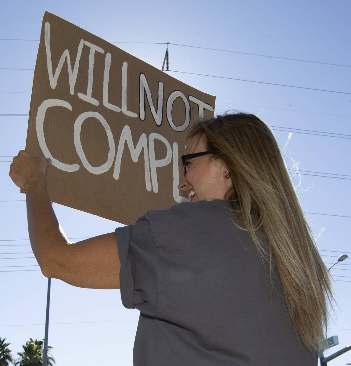 """Anji Gardiner holds up a sign reading """"will not comply"""" during the """"No Mask Protest"""" at the int ..."""