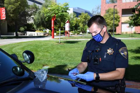 University Police Department officer Ryan Willman checks a bag with credit cards found by campu ...