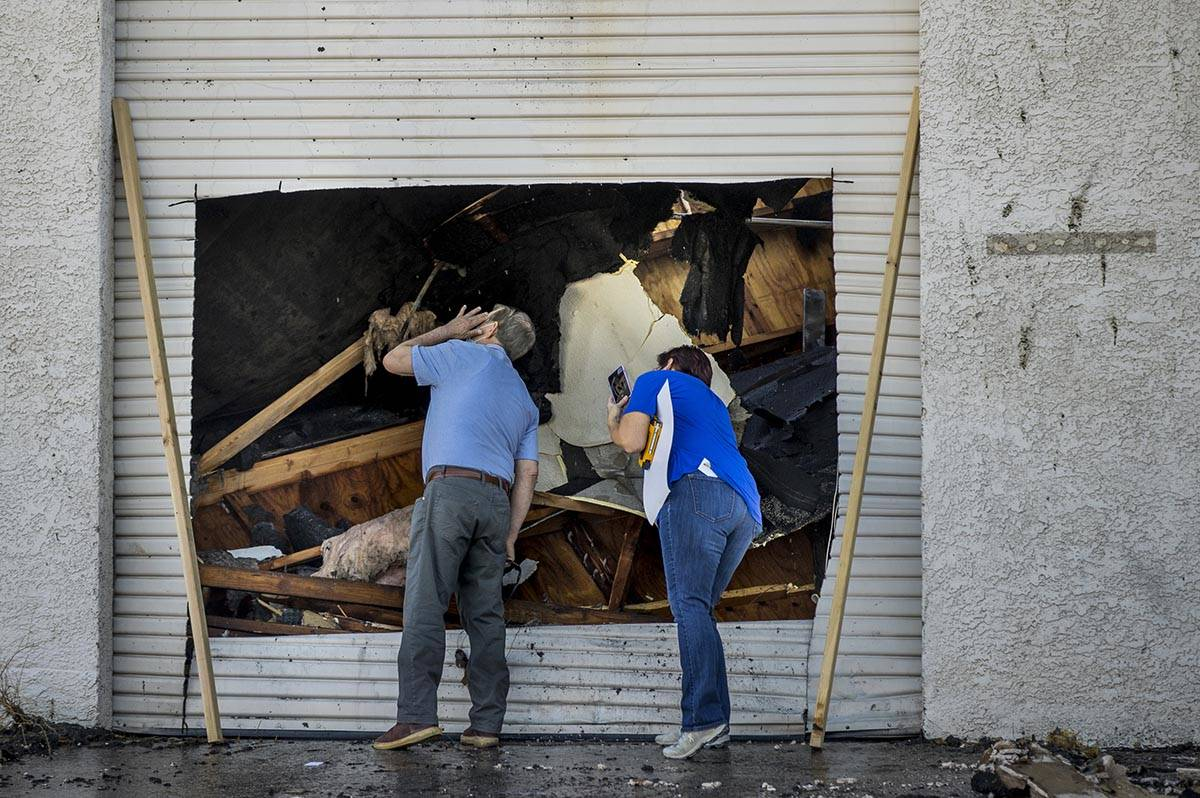 People inspect the damage from an early morning a two-alarm fire in a commercial structure near ...